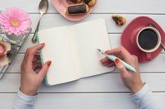 La mujer da el dibujo o la escritura con la pluma de la tinta en cuaderno abierto en la tabla de madera blanca Imagen de archivo