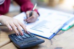 La mujer da el trabajo con la calculadora sobre financiero personal fotos de archivo libres de regalías