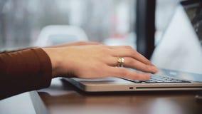 La mujer da el trabajo en el ordenador portátil en la derecha del resbalador del café almacen de video