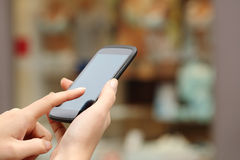 La mujer da la compra en línea con un teléfono elegante Fotos de archivo