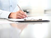 La mujer da la escritura en el tablero con una pluma, aislada foto de archivo