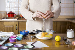 La mujer da la fractura de un huevo para hacer las magdalenas Imágenes de archivo libres de regalías
