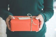 La mujer da llevar a cabo la Navidad caja de regalo hecha a mano o Año Nuevo presente con el fondo de la nieve Imagen de archivo libre de regalías