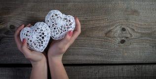 La mujer da llevar a cabo los corazones blancos del cordón en viejo fondo de madera. imagen de archivo