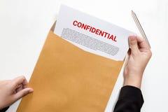La mujer da llevar a cabo y la mirada del documento confidencial en enve imagenes de archivo