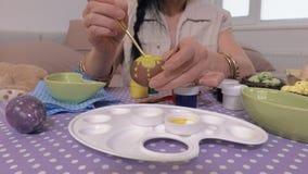 La mujer da los huevos de Pascua de pintura