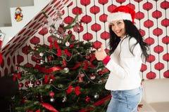 La mujer da los pulgares delante del árbol de Navidad Foto de archivo libre de regalías