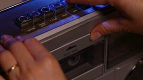 La mujer da a lugar una cinta de casete compacta de música en jugador retro almacen de metraje de vídeo