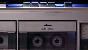 La mujer da a lugar una cinta de casete compacta de música en jugador retro metrajes