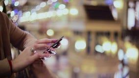 La mujer da mandar un SMS, usando smartphone en alameda metrajes