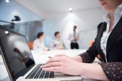 La mujer da mecanografiar en el teclado del ordenador portátil en la reunión de negocios Imagen de archivo