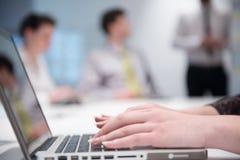 La mujer da mecanografiar en el teclado del ordenador portátil en la reunión de negocios Fotografía de archivo libre de regalías