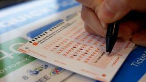 La mujer da número afortunado de relleno en boleto de lotería magnífico diario metrajes