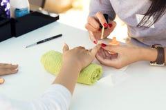 La mujer da la recepción de una manicura en salón de belleza, al aire libre festival de la belleza Limadura del clavo fotografía de archivo