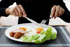 La mujer da sostener el cuchillo y la bifurcación durante la consumición del desayuno foto de archivo
