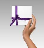 La mujer da sostener la actual caja blanca del día de fiesta con la cinta púrpura en un fondo blanco Foto de archivo libre de regalías