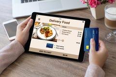 La mujer da sostener la tableta de la tarjeta de crédito con la comida de la entrega del app Fotografía de archivo