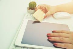 La mujer da sostener la tarjeta de crédito y usar el ordenador portátil imagenes de archivo
