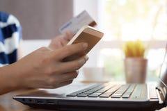 La mujer da sostener la tarjeta de crédito y usar el teléfono elegante imagenes de archivo