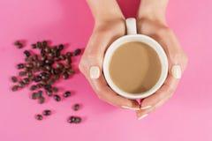 La mujer da sostener la taza de café y de granos de café borrosos en el escritorio rosado Imagen de archivo libre de regalías