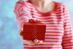 La mujer da sostener un regalo o una actual caja con el arco de la cinta roja para el día de tarjetas del día de San Valentín Fotografía de archivo