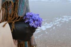 La mujer da sostener una flor con el foco en una flor, mar, invierno Foto de archivo libre de regalías