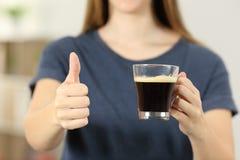 La mujer da sostener una taza de café con los pulgares para arriba Fotos de archivo libres de regalías