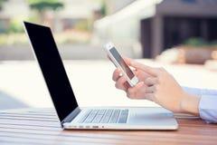 La mujer da sostener, usando el teléfono elegante, móvil y el ordenador Foto de archivo libre de regalías
