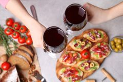 La mujer da tostar con los vidrios de vino rojo Foto de archivo libre de regalías