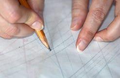 La mujer da trasing en el papel el detalle para coser Fotos de archivo