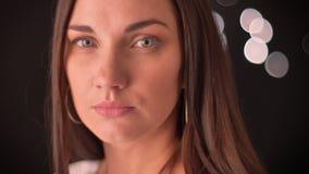 La mujer da vuelta hacia la cámara y mira directamente en ella en un fondo de las blured-luces almacen de video