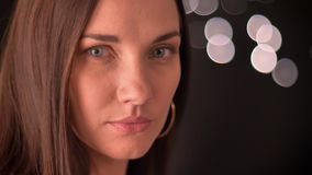 La mujer da vuelta hacia la cámara y tienta en un fondo de las blured-luces almacen de video