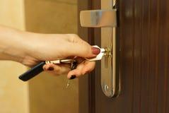 La mujer da vuelta a la llave en una cerradura en una puerta externa Fotografía de archivo libre de regalías