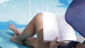 La mujer da vuelta a la página del libro cerca de la piscina almacen de metraje de vídeo