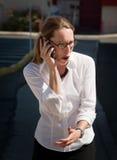 La mujer dada una sacudida eléctrica y sorprendente habla en el teléfono celular Fotografía de archivo libre de regalías