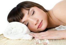 La mujer dark-haired hermosa se relaja en un masaje p Foto de archivo