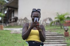 La mujer de África toma las fotos con el teléfono imagenes de archivo
