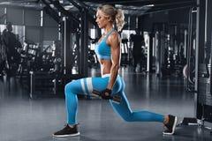 La mujer de la aptitud que hace estocadas ejercita para el entrenamiento del entrenamiento del músculo de la pierna en gimnasio M imagen de archivo