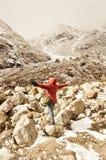 La mujer de Asia del caminante en vestido rojo da vuelta a retroceder y a estirar sus brazos aumentados en cielo después de camin imagenes de archivo