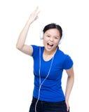La mujer de Asia escucha la música con el auricular Imagenes de archivo