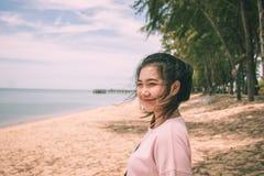 La mujer de Asia que sonríe en la mirada de la playa tiene gusto feliz Imagenes de archivo