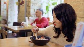 La mujer de Bautiful intenta un plato tradicional sabroso en restaurante coreano almacen de metraje de vídeo