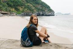 La mujer de Beaty se está sentando cerca del mar y está mirando la cámara Fotos de archivo libres de regalías