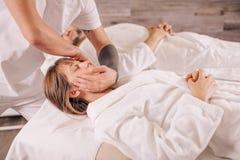 La mujer de la belleza está consiguiendo el masaje principal mientras que su marido que miente en la cama fotografía de archivo