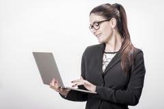 La mujer de carrera acertada joven sostiene su ordenador portátil Imagenes de archivo