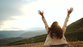 La mujer de celebración feliz del éxito que ganaba en la colocación de la puesta del sol o de la salida del sol regocijó con los  metrajes