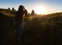 La mujer de celebración feliz del éxito que ganaba en la colocación de la puesta del sol o de la salida del sol regocijó con los  fotografía de archivo