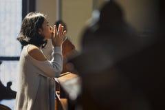 La mujer de Christian Asian ruega en la iglesia imagen de archivo