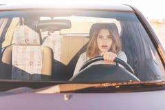 La mujer de conducción temerosa, aprende conducir el automóvil, hembra atractiva se sienta en la rueda solamente por la primera v imagen de archivo libre de regalías