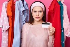 La mujer de Dicontent sostiene la tarjeta de crédito y mira subrayó, ella tiene problemas financieros La hembra morena gasta todo imágenes de archivo libres de regalías